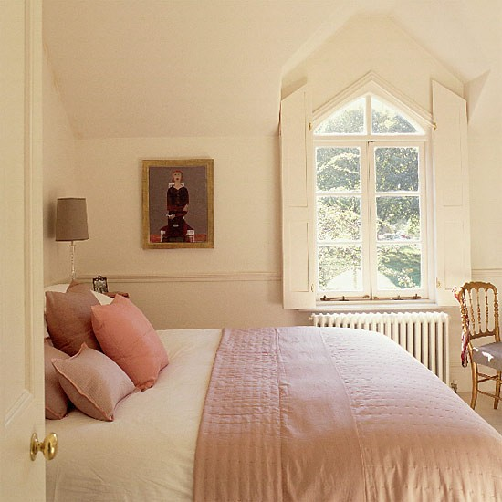 small cream bedroom with gothic windows and silk quilt