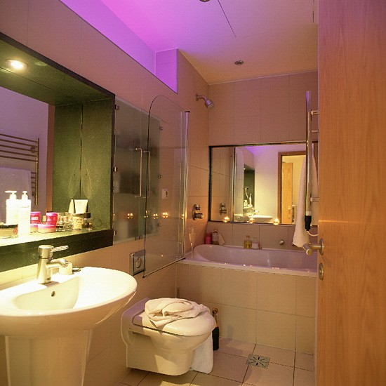 Small bathroom with white suite and mirrors housetohome for Space saving bathroom designs