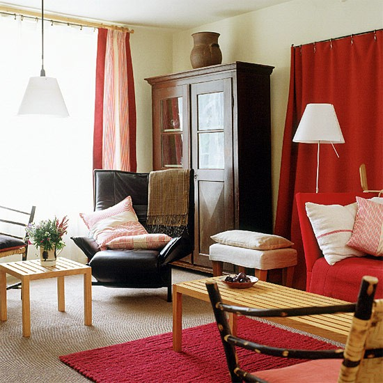 Living Room With Red Rug And Curtains And Mixed Furniture