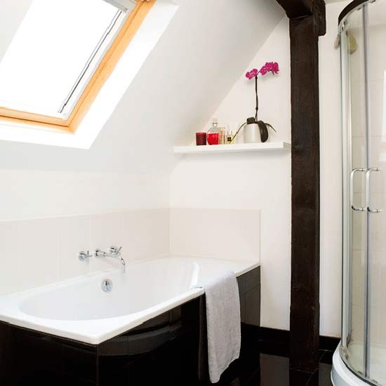 Small white en-suite attic bathroom with skylight
