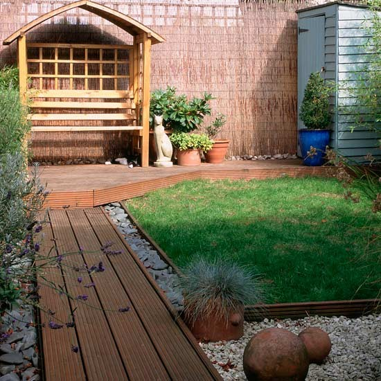 Small garden with decked path and wooden arbour