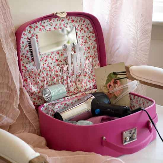 Pink suitcase with hairdryer, rollers and clips inside