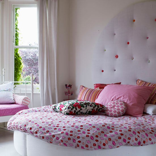 Luxurious girly bedroom with pink bedding and headboard