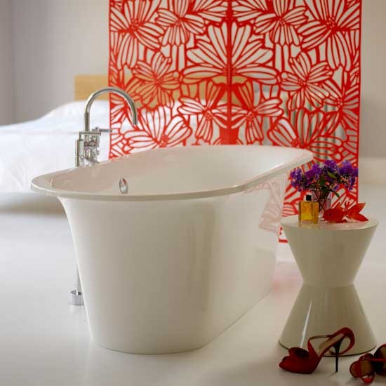 White freestanding bath with orange patterned screen