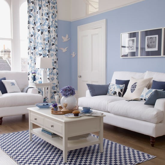 Add definition to a light blue living room with accents in a darker shade