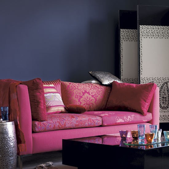 Team dark walls with a brightly-coloured sofa to create a style statement