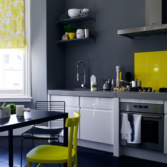 charcoal grey kitchen with white gloss units and yellow splashback