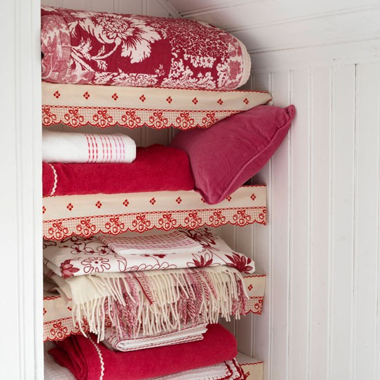 Red and white cushion and throws on white shelves