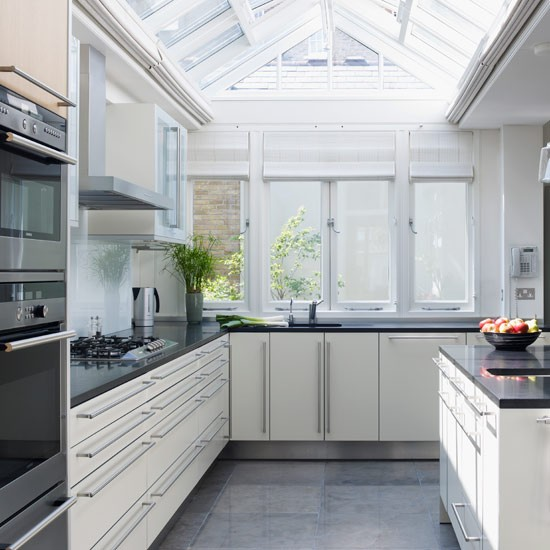 Kitchen extension with skylight, white cabinetry and black worktops