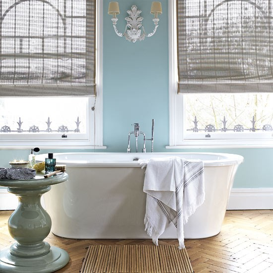 White free-standing bath, with blue walls and large sash windows