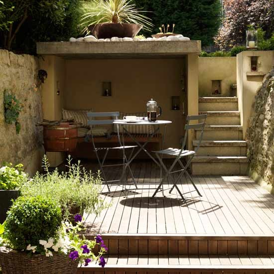Small garden with decking, wooden table and chairs
