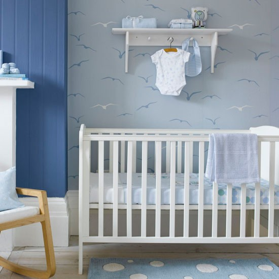 Child's nursery with white cot and seagull print wallpaper