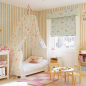 Spacious girl's bedroom with canopy bedding an floral print blind