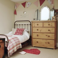 Girl's bedroom with bunting and iron bedstead