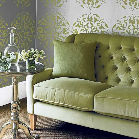 both reflects the green of the sofa as well as light into the room