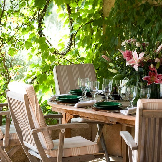 Wooden garden furniture on decking with green tableware