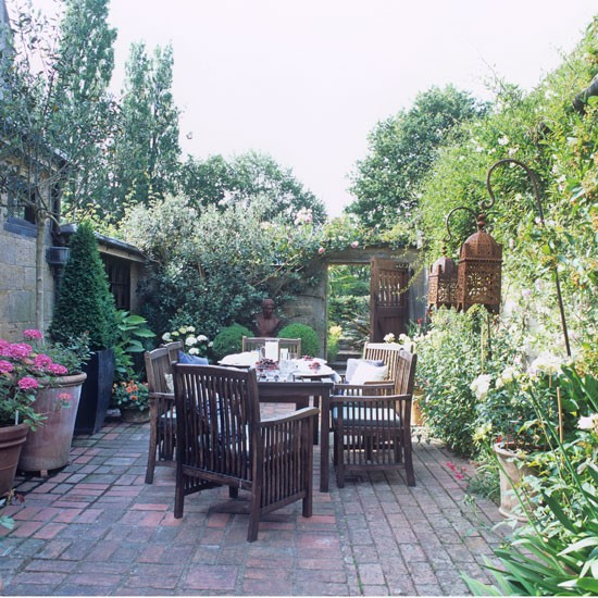 Brick paved terrace with large wooden table and chairs