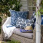 Wicker bench on garden patio with blue and white cushions