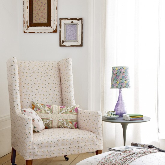 Cream arm chair with speckled grey dots, next to a side table with purple table lamp