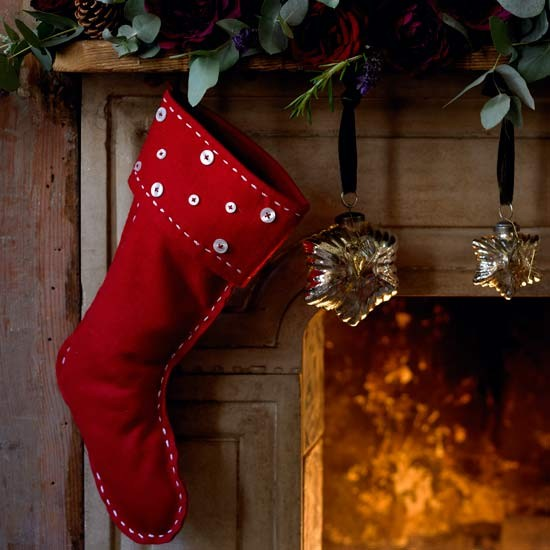fireplace decorated with red felt stocking eucalyptus rose blooms