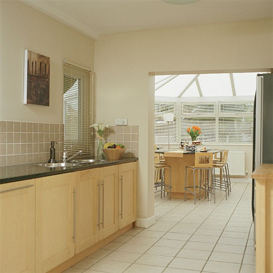 Kitchen extension with neutral floor tiles, wood cabinetry and grey worktops