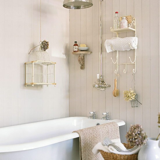 Small cream bathroom with rolltop bath and vintage-style racks