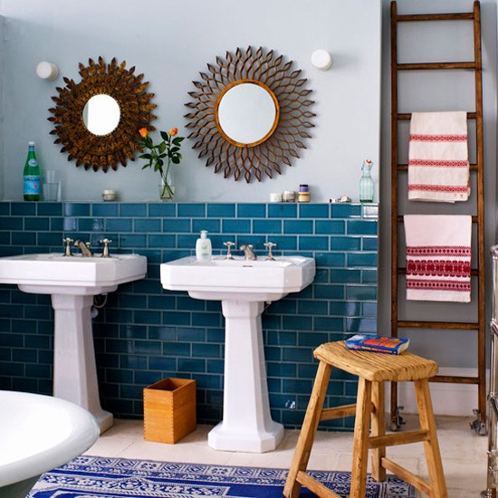 Two white bathroom sinks with blue tiled walls and circular mirrors