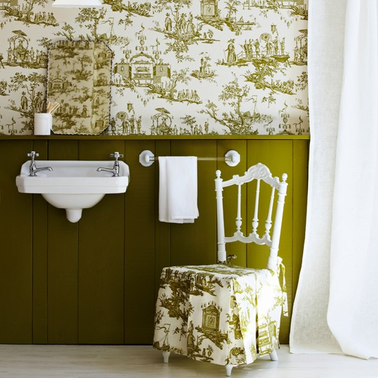Printed green and white wallpaper with matching chair and white basin