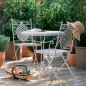 Patio with wrought iron rustic table, chairs and potted trees