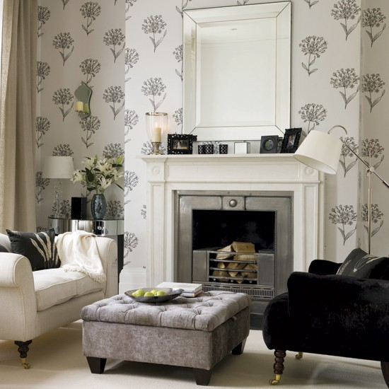 Monochrome living room with floral wallpaper, armchairs, footstool, mirror above fireplace and side table.