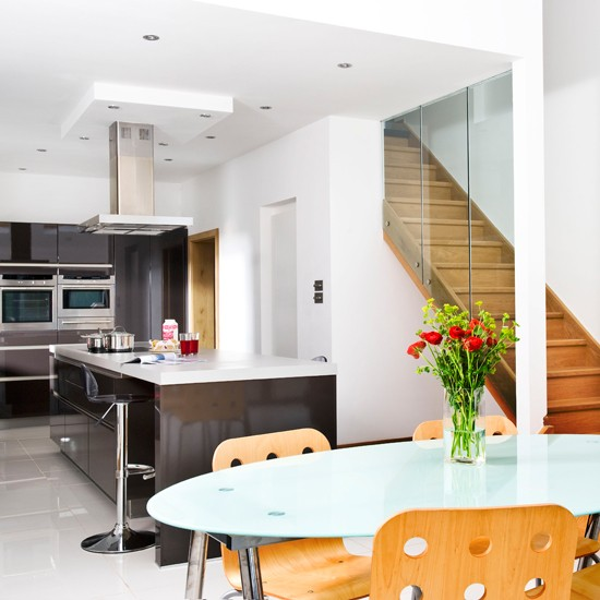 Clean-lined modern fitted kitchen with table, chairs and wooden stairs.