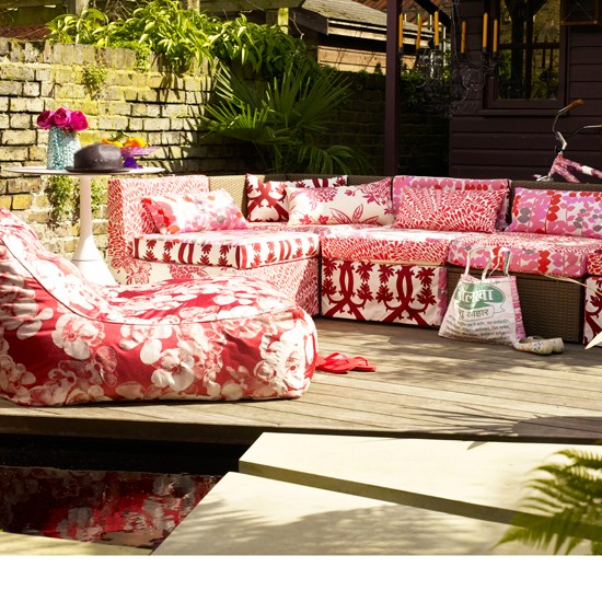 Red patterned garden seating on decking with circular table