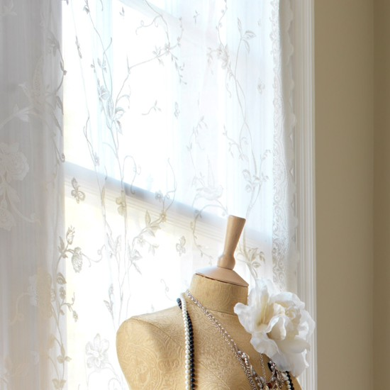 Window with lace curtain behind dress mannequin