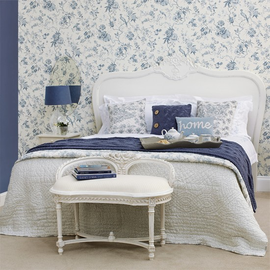 Blue and white floral theme, double bed with occasional chairs at end of bed