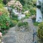 Country garden with gravel path and green bench