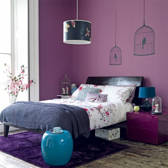 Purple walls, double bed, bedlinen, ceiling light and bedside table with wall stickers