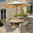 Turnberry South American oak table, £905; Antibes parasol, £300; Pesaro wicker chairs, £220 each, 