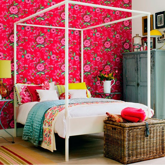 bold floral wallpaper backdrop to four poster bed wardrobe bedside