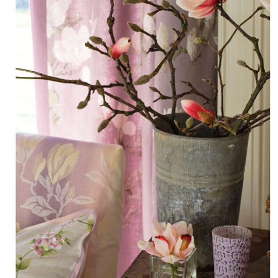 Decorative floral display in metal jug, against floral curtains and soft furnishings.