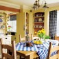 Farmhouse kitchen with pale yellow walls, built-in shelving, wooden dining set and gingham tablecloth