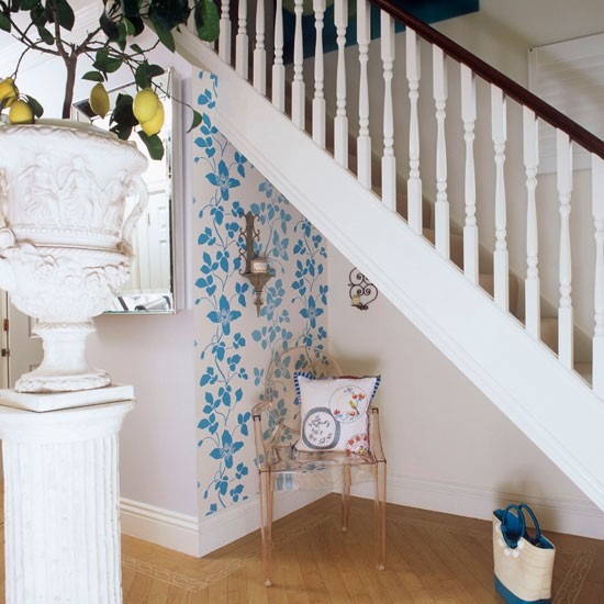 Small hallway with white banisters, wood flooring and blue wall stencil