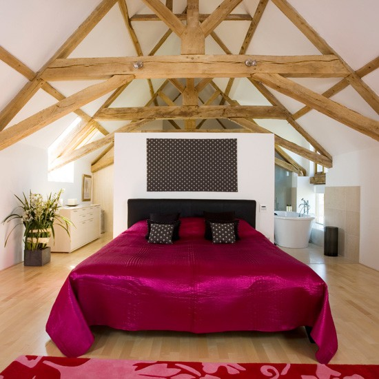 Double bed with red satin cover in a large room
