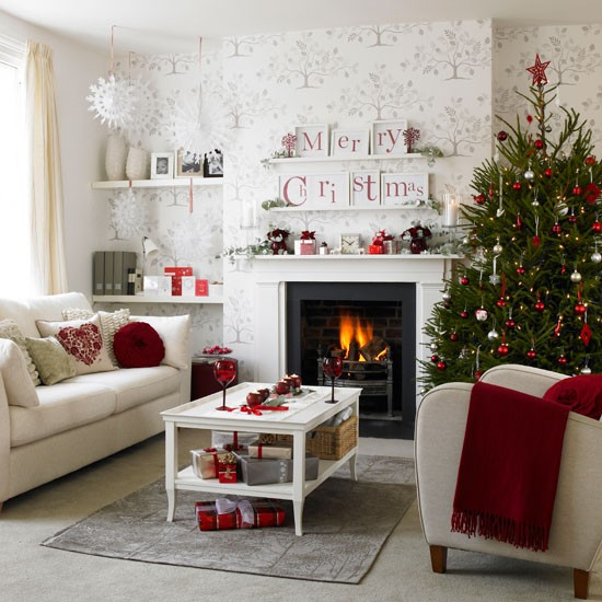 Christmas living room with tree wallpaper, white fireplace, neutral sofas and red blanket