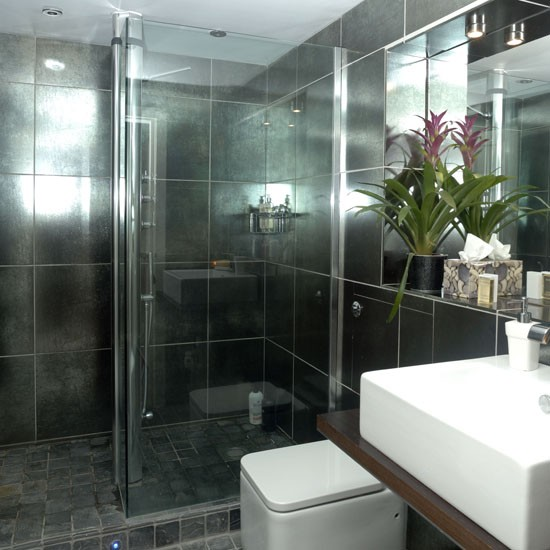 Shower room with grey tiles, walk-in shower, white basin and white toilet