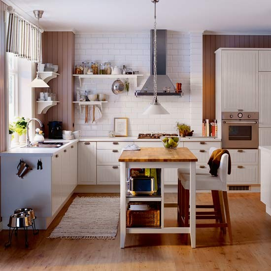 Kitchen with wood flooring, white cabinetry and freestanding kitchen island with wood worktop