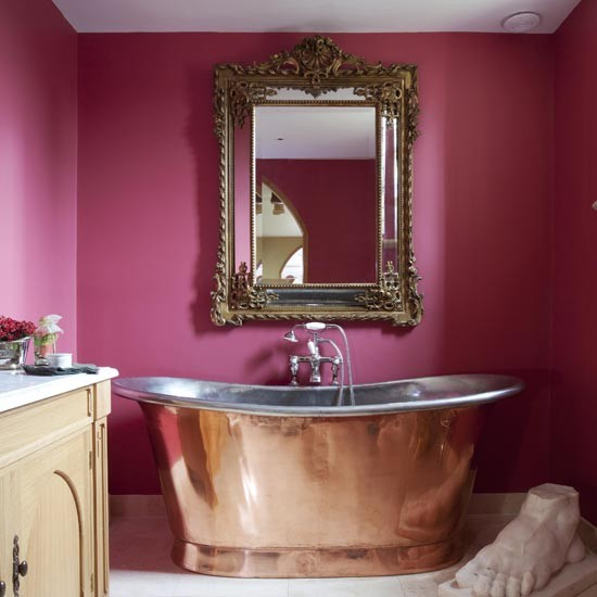 Copper bath in front of pink painted walls with ornate mirror