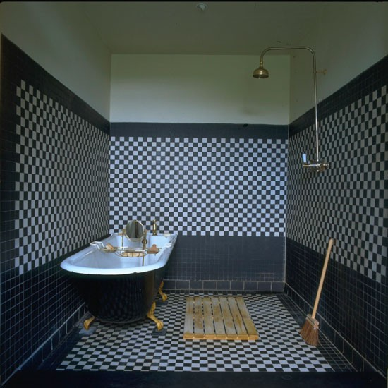 Black and white tiled bathroom with free-standing bath