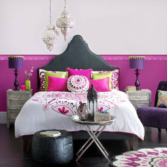 Moroccan vibrant pink bedroom with ornate headboard, pouff, metal furniture and lanterns