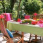 Patio with wooden dining set, red picnicware and green tablecloth