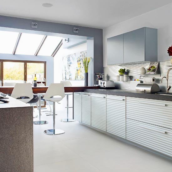 Kitchen extension with skylight, white textured cabinetry and composite kitchen island